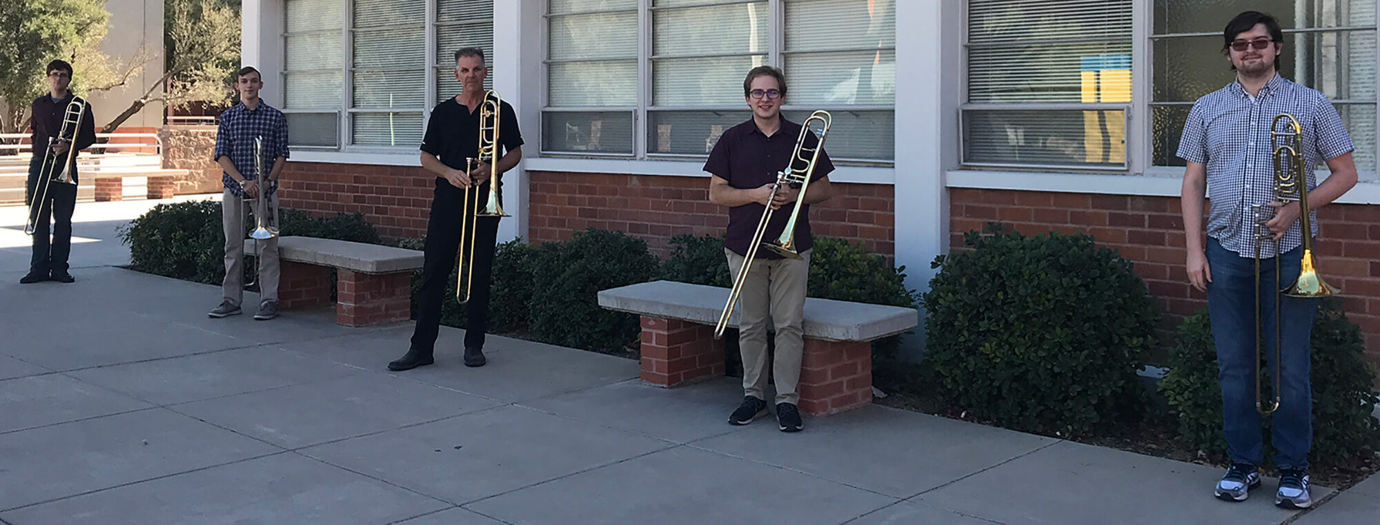 Photo of Trombone Studio students and instructor in front of the Fred Fox School of Music building
